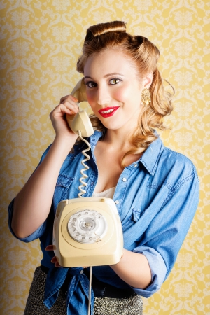 Retro Lady Wearing Denim Shirt And Leopard Print Skirt Chatting On The Home Phone Against Yellow Wallpaper Background  photo