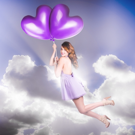 Beautiful Vintage Girl With Retro Hair Style Wearing Purple Pin-Up Fashion Flying High In The Sky On The Whim Of A Love Heart Balloon Romance photo