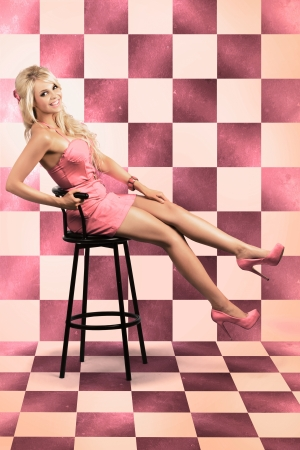 Beautiful Retro Lady In Pink Rockabilly Dress Sitting On Bar Stool Inside Retro Diner In A Depiction Of 60s American Pin Up Culture Stock Photo - 18030306