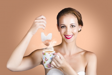 Classy British Brunette Woman Drinking Tea Or Coffee While Dangling A Heart Shaped Teabag Or Coffee Satchel In A Depiction Of Hot Beverage Love photo
