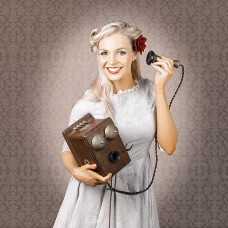 Old Fashioned Portrait Of A Classical Woman Receiving A Happy Phone Call Through The Receiver Of A Box Telephone In A Good News Concept photo
