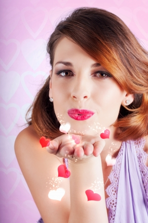 Portrait of a young woman blowing kiss with hearts photo