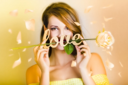 Young woman standing under a fall of flower petals holding white rose entwined with love text on yellow background photo