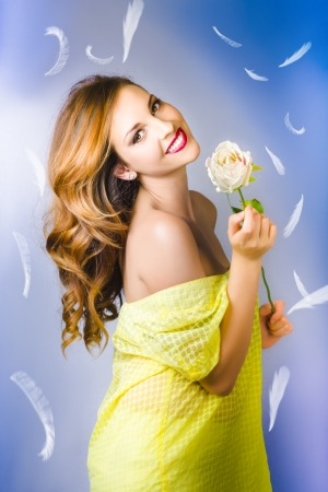 Smiling woman holding a white rose with feathers on the blue background photo
