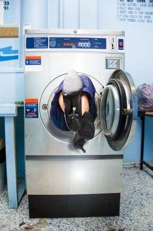 Feet Of A Cleaning Lady Stick Out Of The End Of A Front Loader Washing Machine She Became Trapped In While Trying To Clean In A Humorous House Work Photograph Stock Photo - 18253669