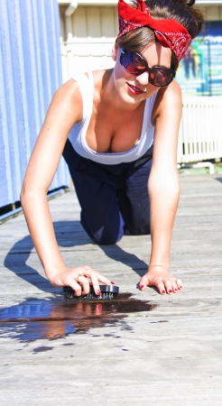 Cross Processed Vintage Image Of A Sexy Retro Housewife Scrubbing And Cleaning A Wooden Deck With Water Outdoors Wearing Bandana A Low Cut Top Stock Photo - 18253645