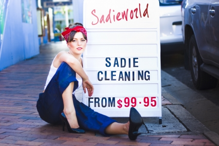 Sadie The Cleaning Lady Marketing Her House Clean And Tidy Service While Sitting Next To A Sadieworld Advertising Sign On The Street photo