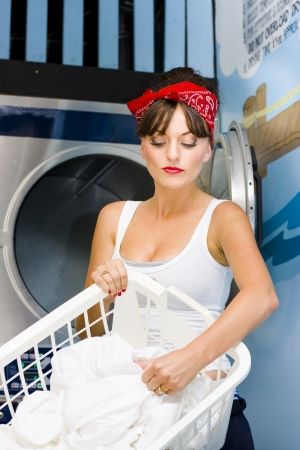 Woman Sorts Her House Bed Sheets and Clothing In Front Of A Front Loading Washing Machine At The Local Laundry Mat While In The Process Of Washing Clothes photo