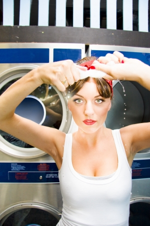 Woman Wrings Out A Wet Cloth In A Laundromat As Water Droplets Fall To The Ground In A House Work Concept Stock Photo - 18253641