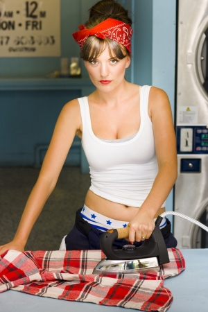 Anger Bitter And Sad House Wife Glares Up While Ironing A Red Flannelette Shirt In The Home Laundry Room In An Unhappy Housewife Concept photo