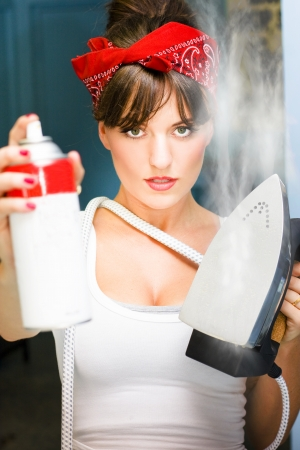 Laundry And Ironing Business Woman In The Action Of Working Holds Up A Bottle Of Iron Spray And A Steaming Hot Iron Press In A Work From Home Concept photo