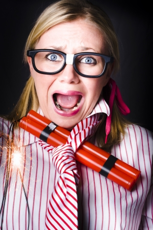 Crazy business woman screaming with lit bomb under striped tie while a deadline of explosive stress looms photo