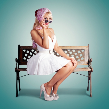 Classic Fashion Portrait Of A American Blond Beauty Sitting On A Park Bench Wearing Fashionable Headscarf, Sunglasses And White Retro Dress. On Green Background photo