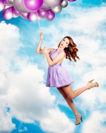 Humorous Beautiful Pin-up Girl Flying In A Cloud Filled Sky While Holding Onto A Rope Of Helium Party Balloons In A Birthday Celebration Concept photo
