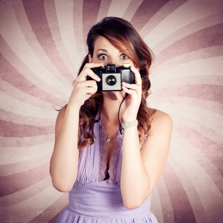 Cute Brunette Pinup Girl With Surprised Expression Pressing Shutter Button On An Old Film Camera While Taking A Vintage Photograph photo