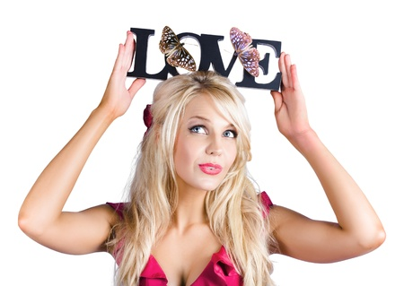 Attractive blond woman in pink dress holding love sign in upper case black text above her head decorated by butterflies on white background photo