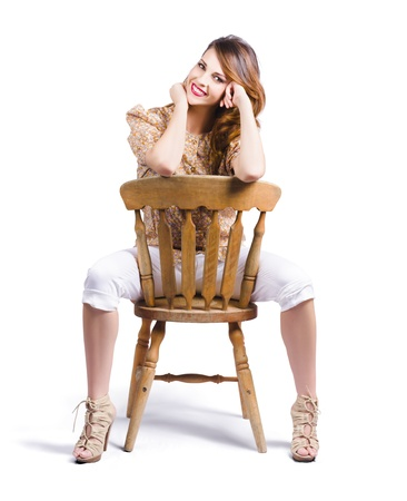Pin-up style woman posing on a chair photo