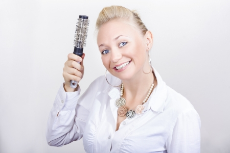 Happy Blond Hairdresser In Beauty Salon Holding Hair Brush While Demonstrating Hair Care Procedures photo