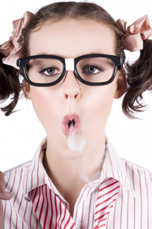 Young nerdy girl wearing eyeglasses blowing smoke from her mouth photo