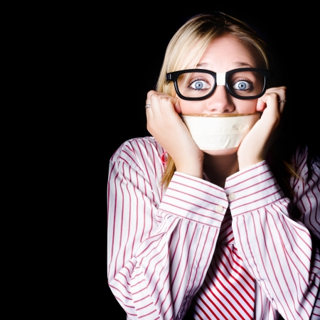 Young nerdy woman wearing eyeglasses, fearful with tape across her mouth photo