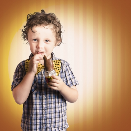 Lovable Little Child Eating Chocolate Easter Bunny Present On Striped Brown Background Stock Photo - 18629236