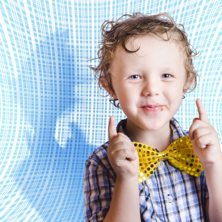 Cute smiling child with chocolate covered face pointing up in approval for Easter time. On blue abstract background Stock Photo - 18629220