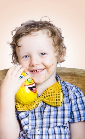 Smiling happy kid with messy chocolate face holding gift egg when celebrating easter holidays Stock Photo - 18629240