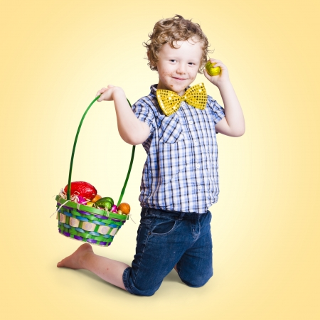 Sweet little child holding easter present with basket full of colourful easter eggs on yellow gradient background Stock Photo - 18629226