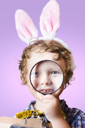 Face of a cute kid wearing pink rabbit ears searching through looking glass during a search and find, easter hunt of discovery Stock Photo - 18629244