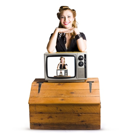 Woman in front of  an unseen TV camera with her picture shown on a television monitor placed on top of a polished pine chest isolated on white background  photo