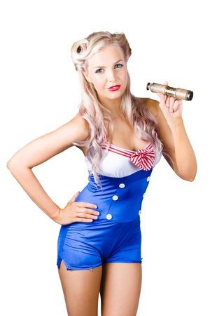 Sexy young woman in red, white and blue sailor outfit with telescope, studio background. photo