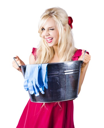 Attractive blond  woman winking wearing  red dress holding big bucket with blue rubber gloves on white background photo