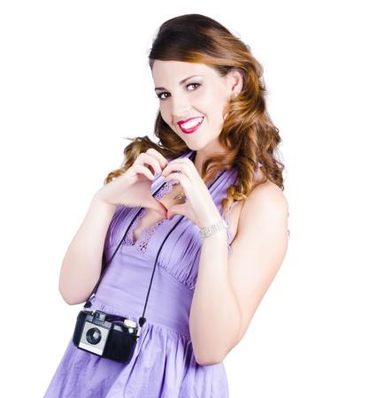 Una mujer con una c�mara haciendo la se�al del coraz�n con sus manos, la fotograf�a encanta el concepto Foto de archivo - 18767559