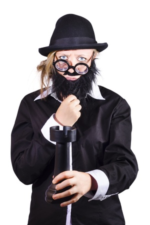 Funny bespectacled woman with black stick-on beard, mustache, homburg hat and jacket holding large  or rook chess piece isolated on white Stock Photo - 18767543