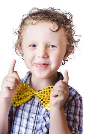 Happy young boy with bow tie pointing upwards, white background Stock Photo - 18767612