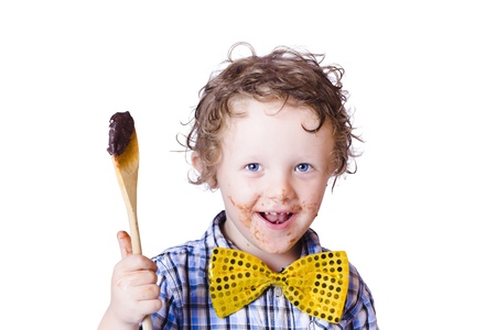 A boy messing with food holding a spoon on a white background photo