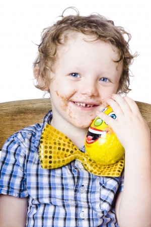 Caucasian boy with blue eyes and curly dirty blond hair wearing blue plaid shirt and sparkly yellow bow-tie. He is holding a yellow egg and has a chocolate smeared face Stock Photo - 18767627