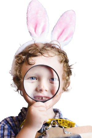 Cute young boy with rabbit ears looking through magnifying glass, Easter hunt concept with white background Stock Photo - 18767563