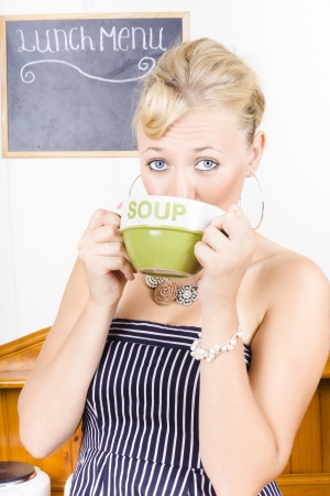 Young retro pin-up woman drinking from a large cup of soup in old-fashion diner photo