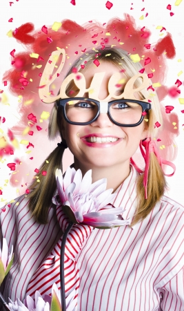 Funny portrait of a romantic nerd girl holding flower while balancing words of love in falling confetti photo