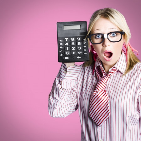 Smart female accountant holding large black calculator with look of shock when discovering a cash surplus on a tax return calculation Stock Photo - 18792134