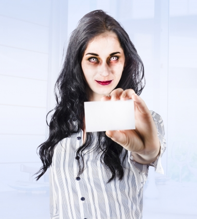 Unfresh female business zombie standing in modern holding business card when killing business stock cliches photo