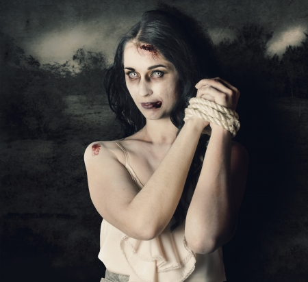 Dark horror scene of an evil zombie woman with hands bound and tied photo