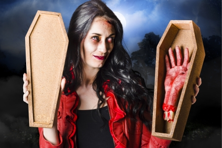 Bloodthirsty dead sexy brunette zombie woman holding open casket photo