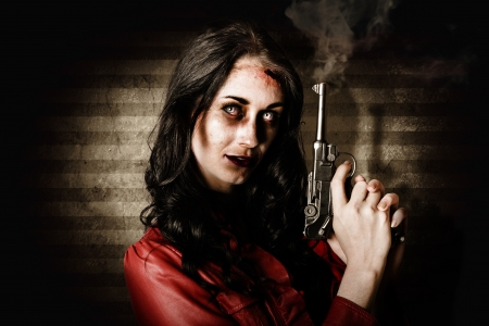Undead female zombie glaring while holding a smoking gun photo