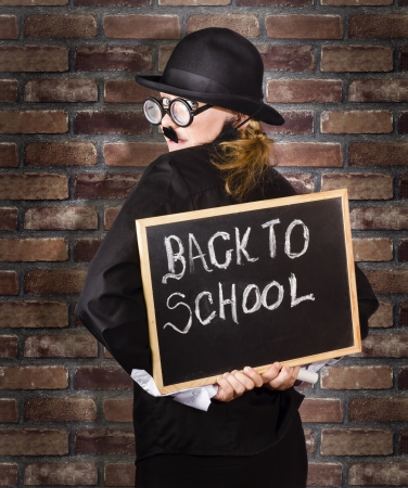 Back of a funny looking headmaster holding black board with back to school written in chalk. School brick wall background photo