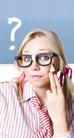 Sweet young blonde girl in geeky glasses with large pencil to face inquiring for an answer to a big question. Chalk board background Stock Photo - 18999660