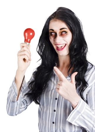 Happy businesswoman in horror makeup pointing at red light bulb, scary idea concept photo