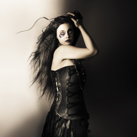 Dark studio portrait of a sexy fashion model  with dark wavy brunette hair wearing black corset and jester make up Stock Photo - 19090073