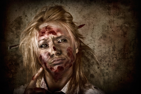 Dark horror portrait of a sinister female zombie businesswoman thinking up a sharp idea with nail through head on grunge background photo